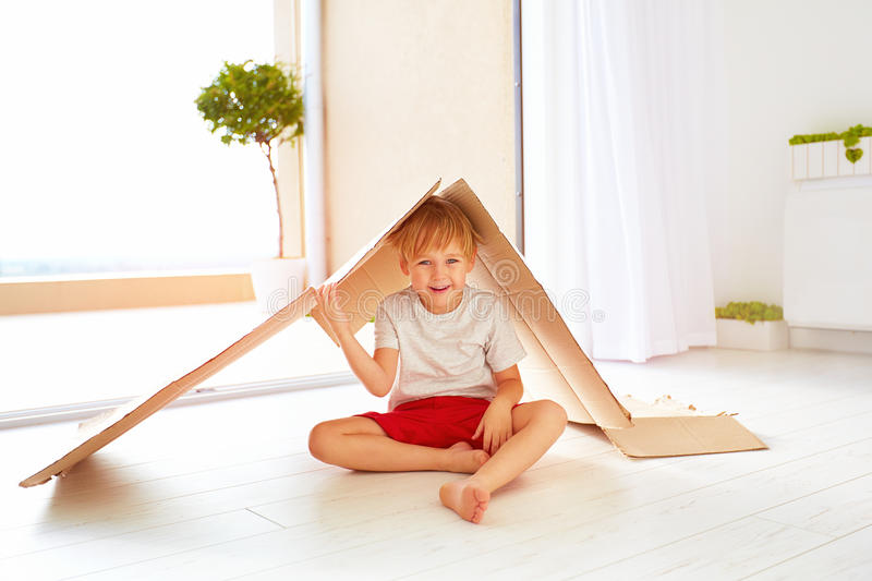 Cute happy boy playing with cardboard box as with toy house royalty free stock photography