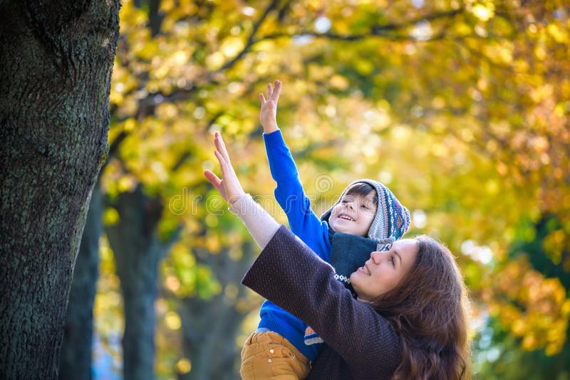 Cute, happy, boy smiling and hugging with his mom among yellow leaves. Little child having fun with mother in autumn park. Concept royalty free stock photo