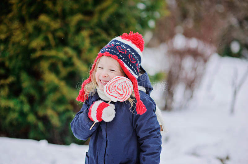 Cute happy child girl with christmas candy in winter garden royalty free stock photography