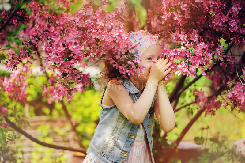 Cute happy child girl in jeans vest enjoying spring near blooming crab apple tree in country garden royalty free stock photography