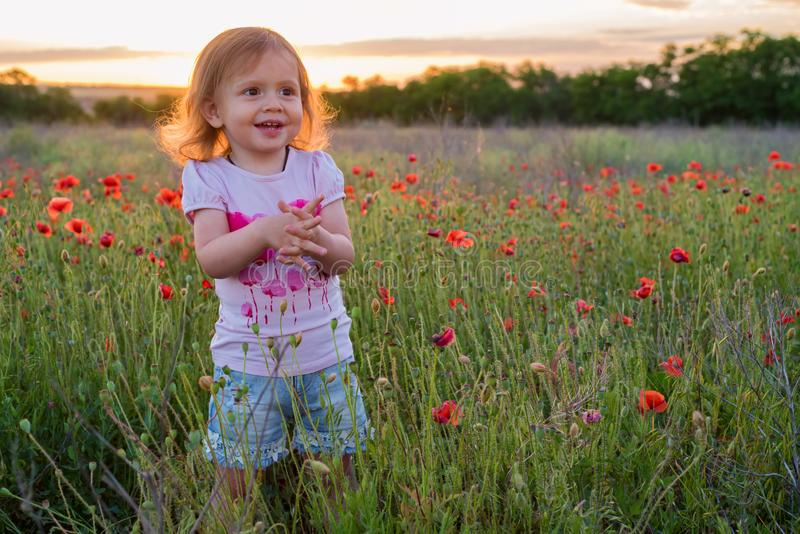 Cute happy child girl in poppy field. Happy childhood concept royalty free stock images