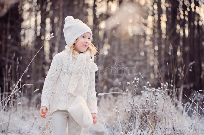 Cute happy child girl portrait on the walk in winter snowy forest royalty free stock photos