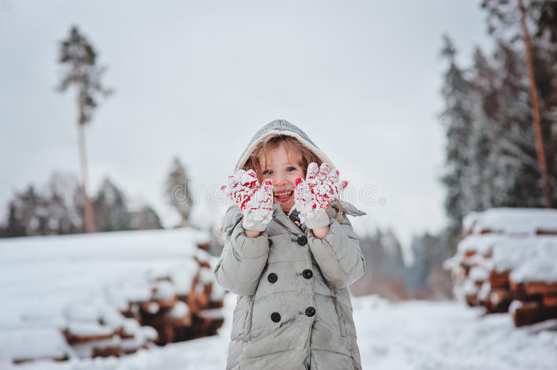 Cute happy child girl portrait on the walk in winter snowy forest stock photo