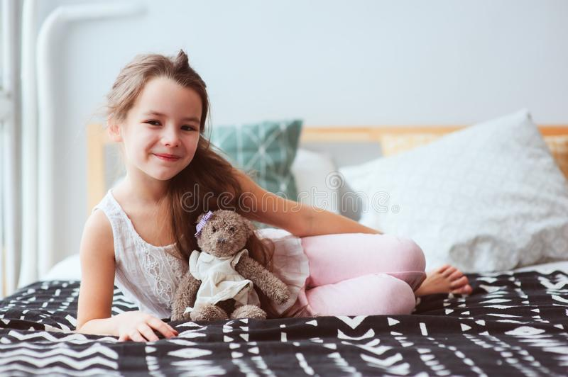 cute happy child girl relaxing at home on the bed in her room in early morning stock photo