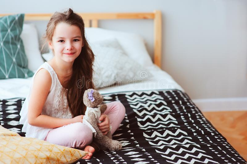 cute happy child girl relaxing at home on the bed in her room in early morning stock images