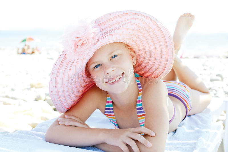Cute happy child lying down on deckchair of beach resort. For summer holidays or travel vacations. Summer vacation idea royalty free stock photos