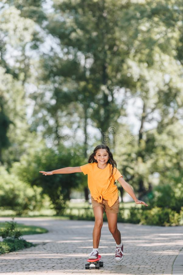 cute happy child riding skateboard and smiling at camera stock photos