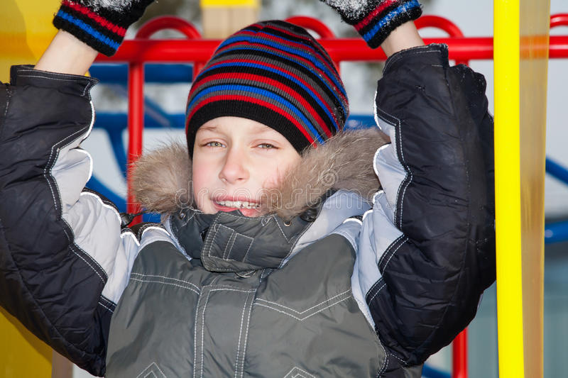 Cute happy child wearing warm jacket and a hat playing at a colorful playground royalty free stock images