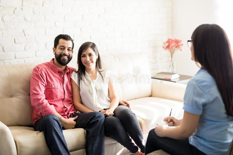 Cute and happy couple with marriage counselor stock photo