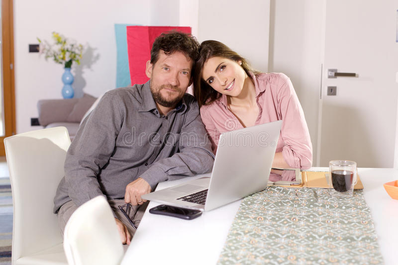 Cute happy couple working from home smiling to camera royalty free stock photography