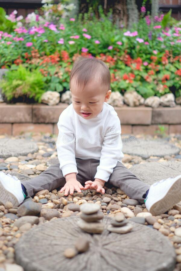Cute happy & curious little Asian 1 year / 18 months old toddler baby boy child sitting on in the beautiful flowers garden holding stock photography