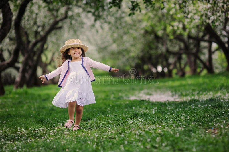 Cute happy dreamy toddler child girl walking in blooming spring garden, celebrating easter outdoor royalty free stock image