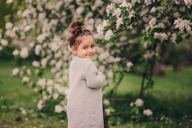 Cute happy dreamy toddler child girl walking in blooming spring garden, celebrating easter outdoor. Cute dreamy toddler child girl walking in blooming spring stock photo