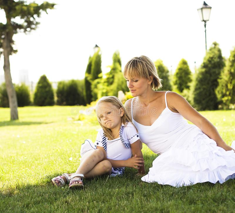 Cute happy family on picnic laying on green grass mother and kid. Warm summer vacations close up, modern people lifestyle together stock photos
