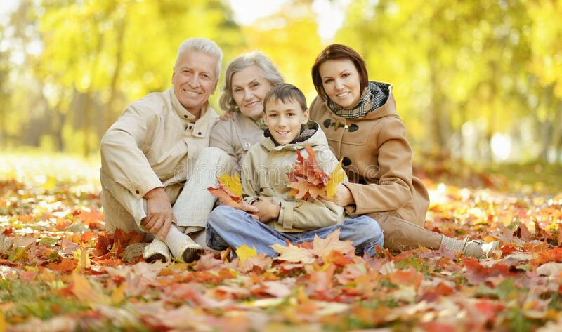 Cute happy family relaxing in autumn forest royalty free stock photography
