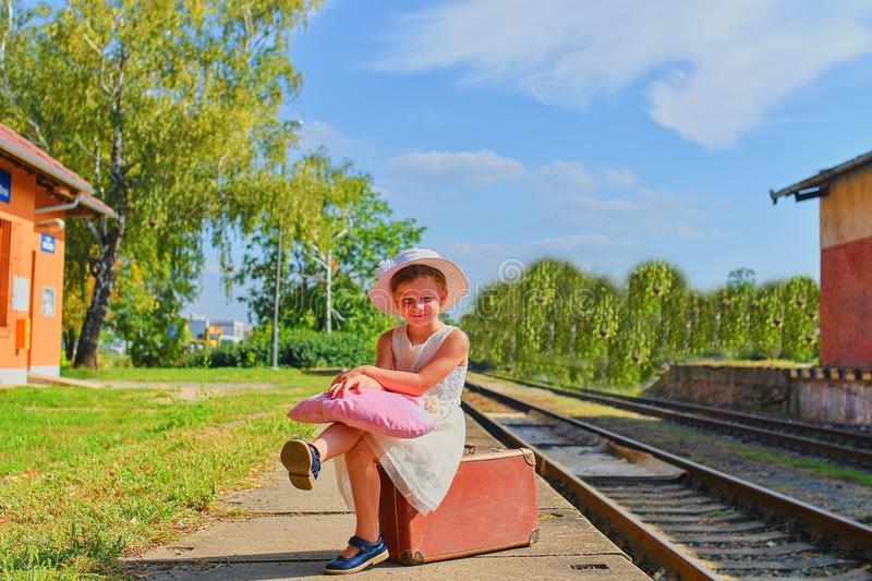 Cute happy girl holding plush toy on a railway station, waiting for the train with vintage suitcase. Traveling, holiday and chilho. Od concept. Travel insurance stock image