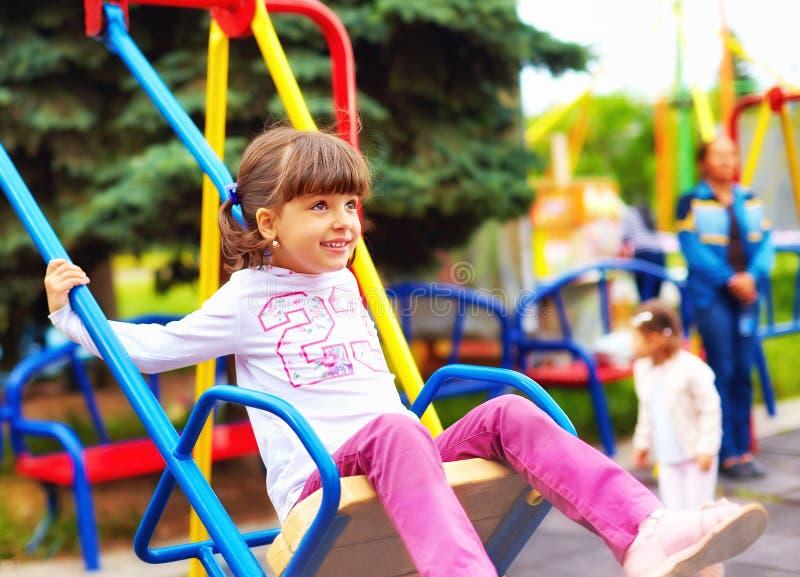Cute happy girl, kid having fun on swings at playground stock photo