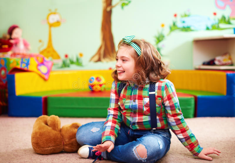 Cute happy girl playing in kindergarten for kids with special needs stock images