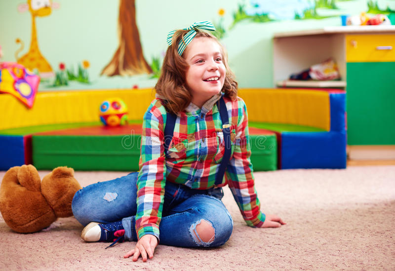 Cute happy girl playing in kindergarten for kids with special needs royalty free stock image