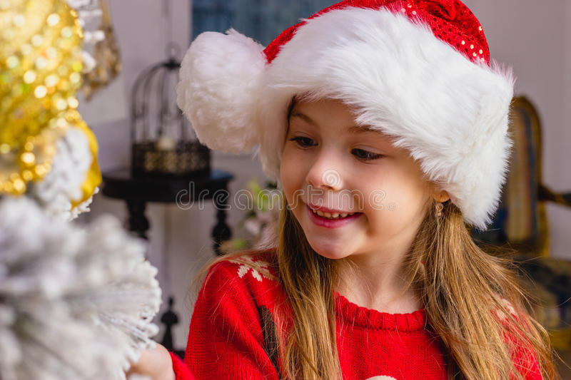 Cute happy girl in red hat hangs decorations royalty free stock photos