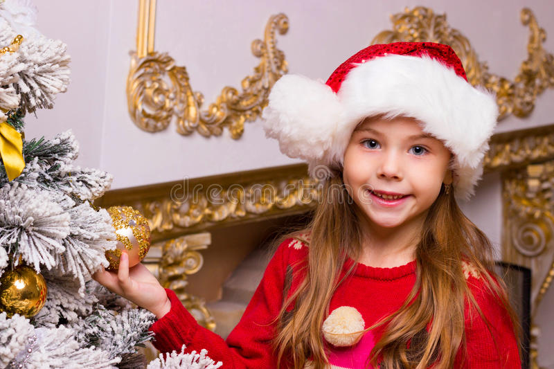 Cute happy girl in red hat hangs decorations royalty free stock image