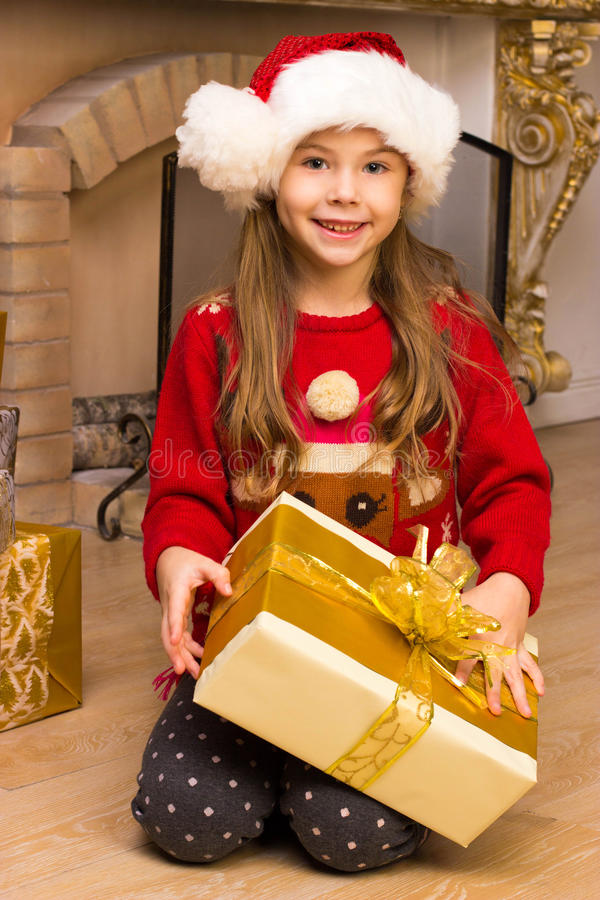 Cute happy girl in red hat holding present royalty free stock images