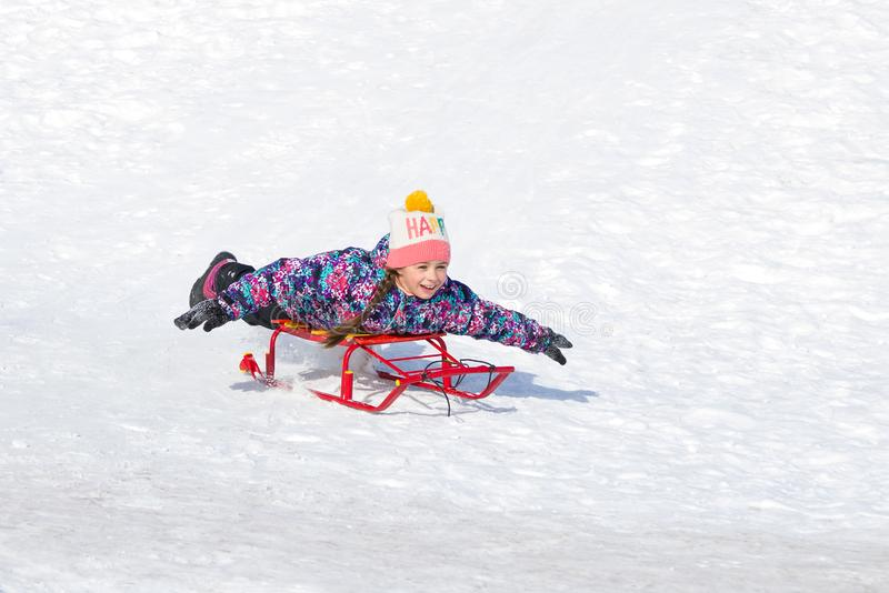 Cute happy girl on a sled sliding down a hill on snow stock images