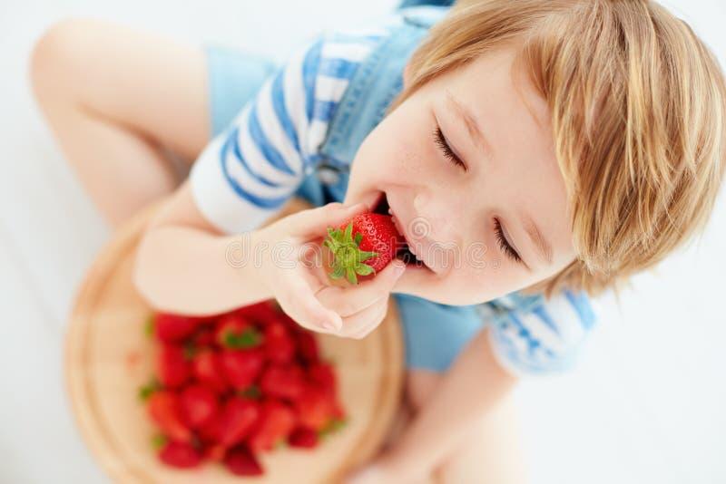 Cute happy kid eating tasty ripe strawberries stock photos