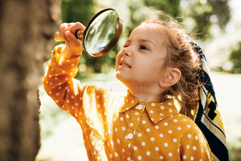 Cute happy kid with magnifying glass exploring the nature outdoor. Adorable little explorer girl playing in forest with magnifying. Glass. Curious child looking stock image