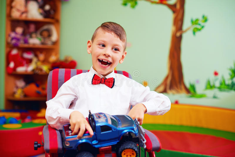 Cute happy kid on wheelchair with present in kindergarten for kids with special needs stock photos
