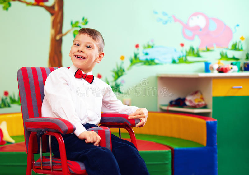 Cute happy kid in wheelchair, wearing glad rags in center for children with special needs royalty free stock image