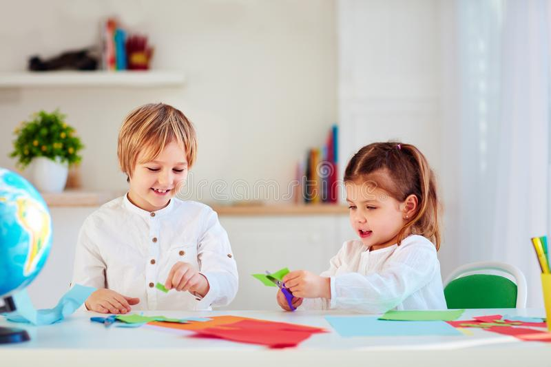 Cute happy kids, boy and girl scissor colorful paper craft at the desk stock photos