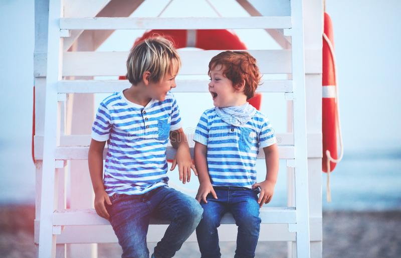 Cute happy kids, brothers laughing together, while sitting on lifeguard tower at the evening beach stock images