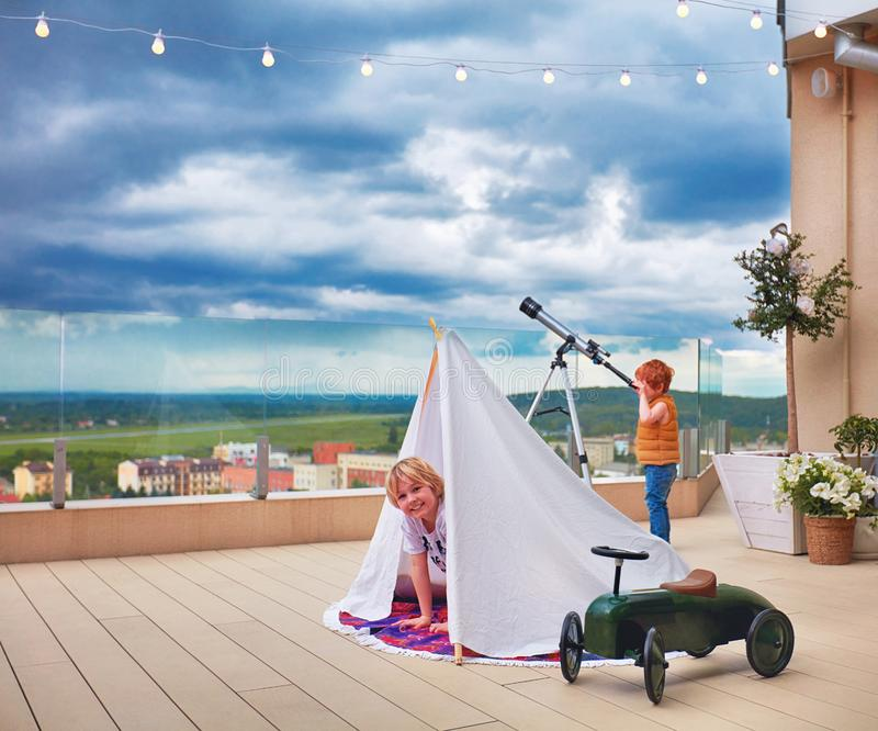 Cute happy kids playing games on the rooftop patio royalty free stock photo