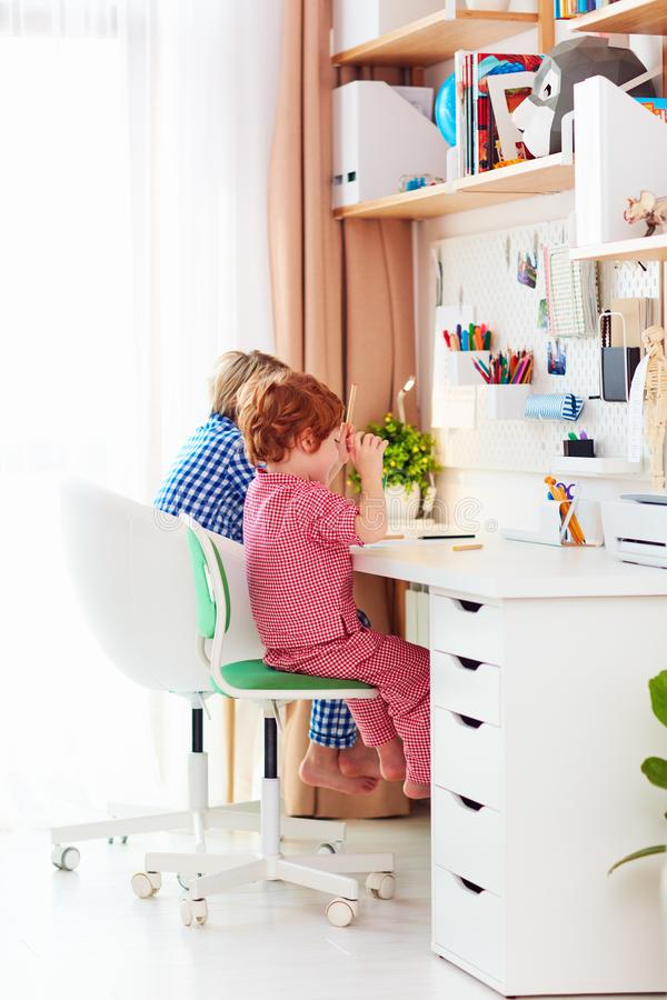 Cute happy kids are sitting together and drawing at the desk at home royalty free stock photography