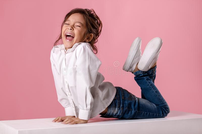 Cute happy laughing little girl in white shirt with hairstyle. On pink background. Human emotions and facial expression stock photography