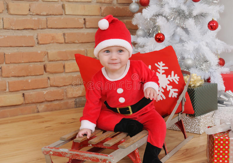 Cute happy little baby boy in Santa suit on old vintage sled wit. H gifts near Christmas tree, happy holiday concept stock image
