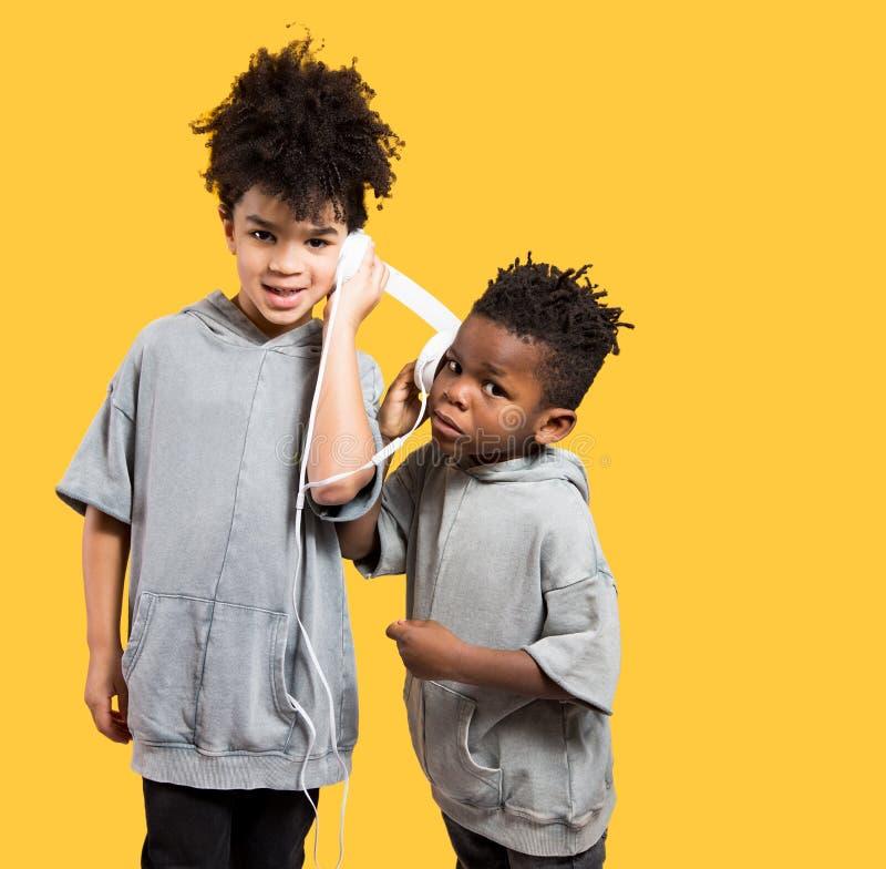Little boys sharing music on headphones stock photos