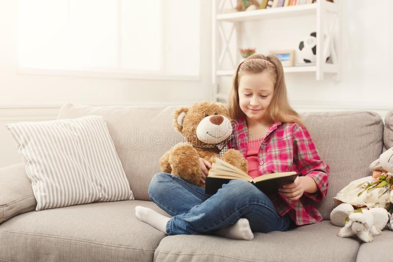 Happy little female child hugging her teddy bear and reading book on sofa at home royalty free stock photo