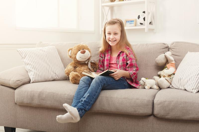 Happy little female child hugging her teddy bear and reading book on sofa at home royalty free stock photos