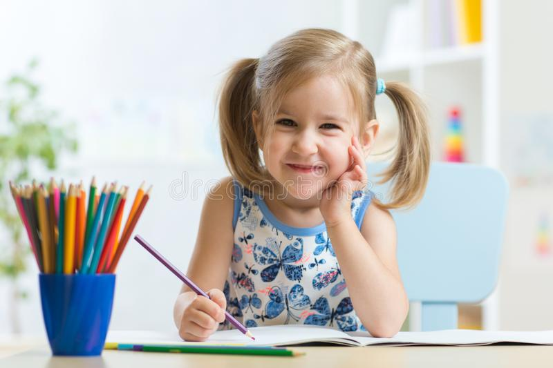 Cute happy little child girl drawing with pencils in daycare center stock photo