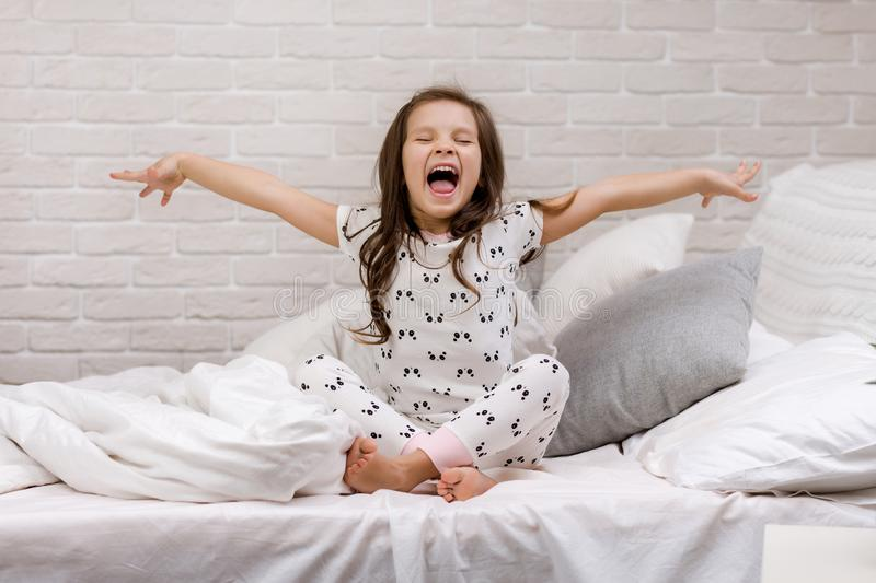 Cute happy little child girl in pyjamas. In bed. good morning royalty free stock photo