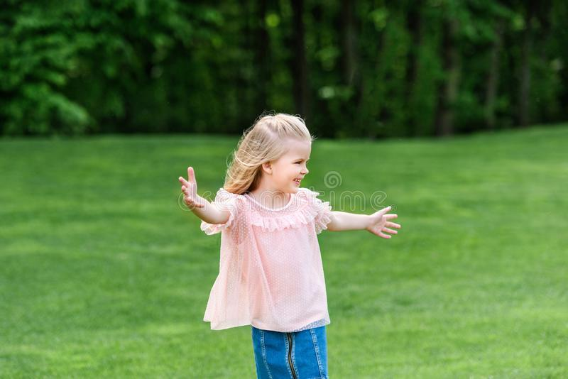 Cute happy little child with open arms looking away. In park stock image