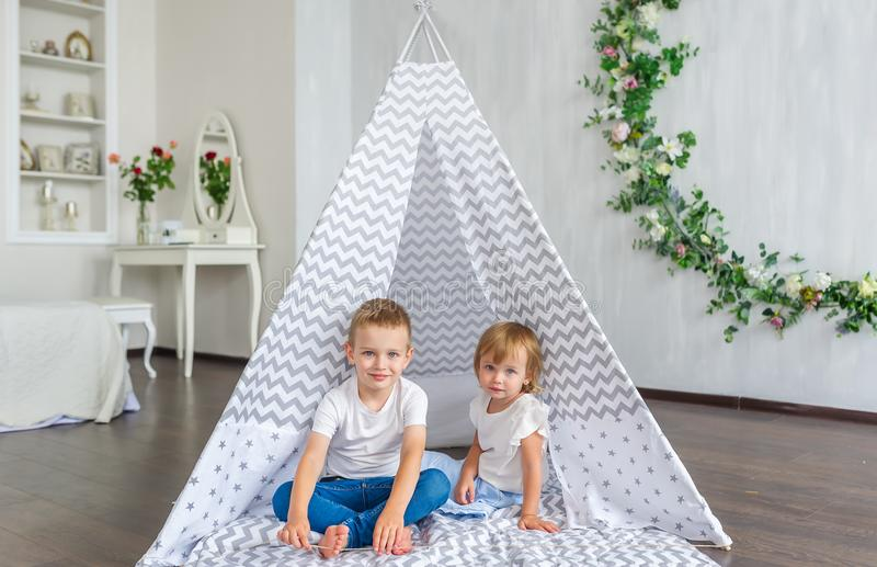 Cute happy little children sitting in teepee at nursery. Horizontal portrait stock image