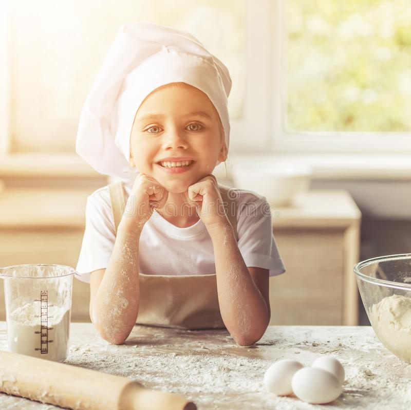 Cute Happy Little Girl in Apron and Chef Hat royalty free stock photo