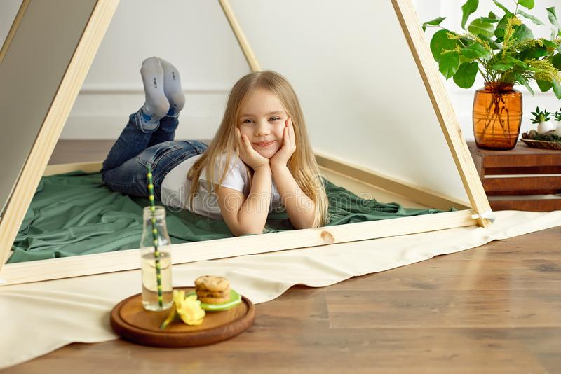 Cute happy little girl playing with toys and dreaming in teepee and bed. royalty free stock images