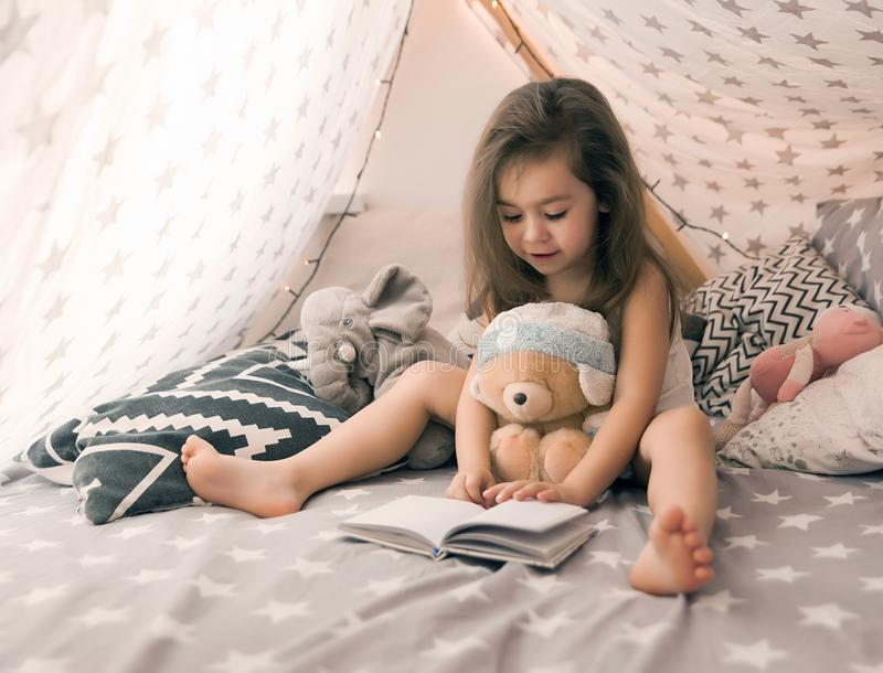 Cute happy little girl playing with toys and reading book in teepee and bed. Close up photo of happy child.  royalty free stock photography