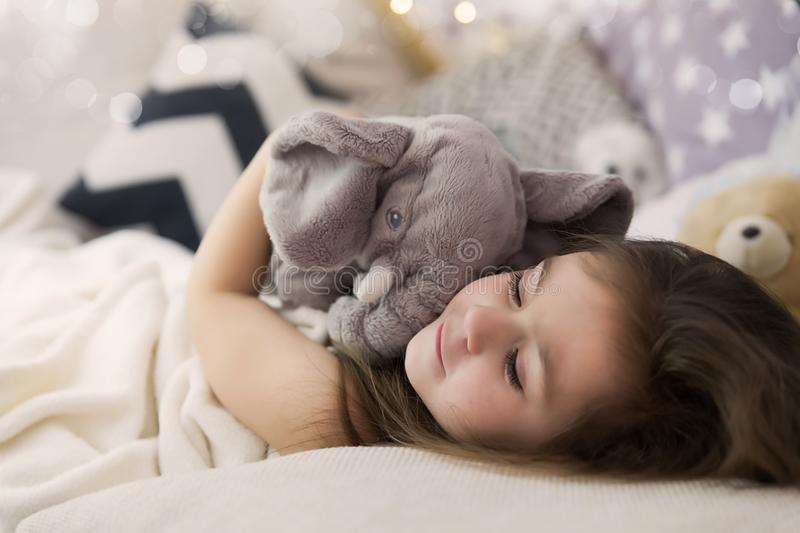 Cute happy little girl sleeping and dreaming in and bed hugging her toy. Close up photo of sleeping child.  stock photography