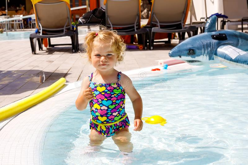 Cute happy little toddler girl in the pool and having fun on family vacations in a hotel resort. Healthy child playing. In water. Baby in colorful fashion royalty free stock photography