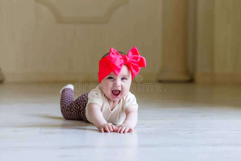 Cute happy 6 months baby girl with bright bow crawling indoor. Pretty smiling baby girl with open mounth. Light stock photos